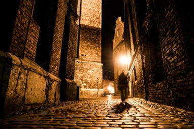 European destinations to spend Halloween | Dark blurred silhouette of person evokes Jack the ripper in illuminated cobbled street in old historical city by night