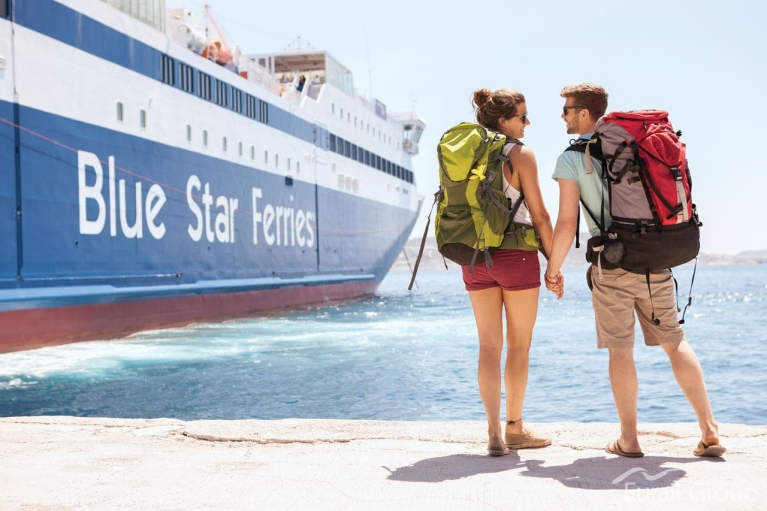 Image of two young backpackers holding hands as the wait beside the ferry