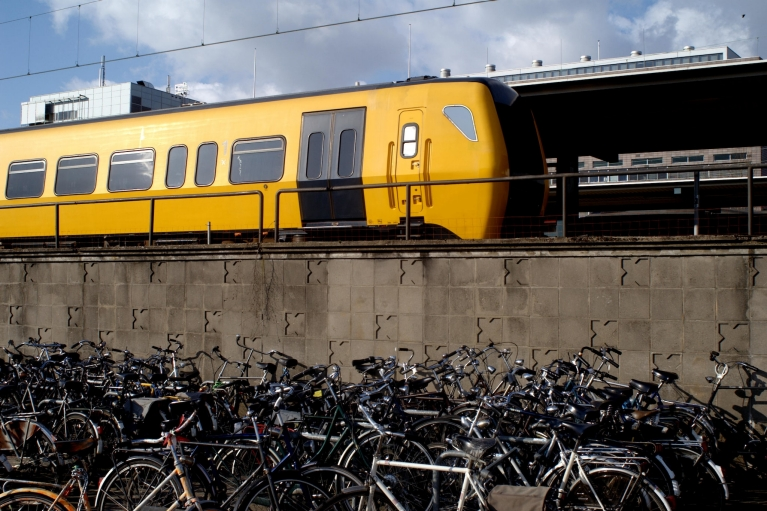 Image of bikes parked by a wall beside a yellow Dutch train
