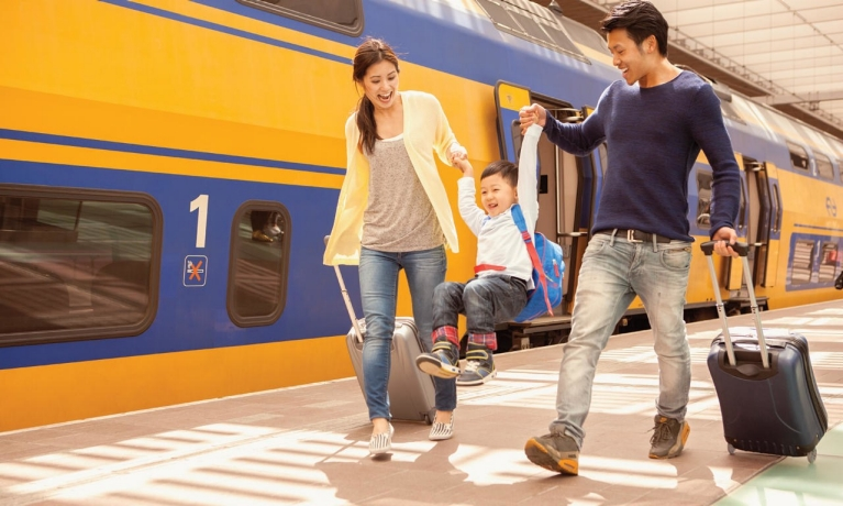 Image of a mother and father carrying their son along a Dutch railway plaform while pulling their cases beside a yellow train
