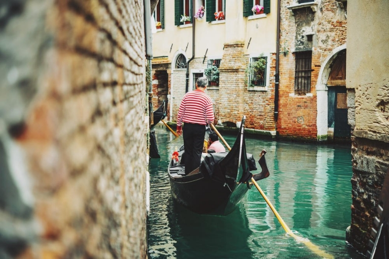 Traditional gondola and gondolier through the canals of Venice