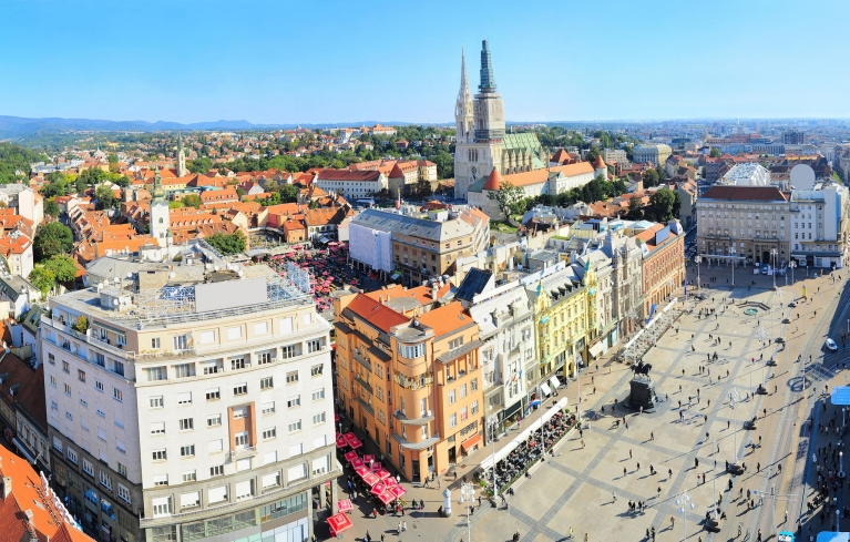 View from high above sunny Zagreb, where people are walking from across the main square to red umbrella covered markets
