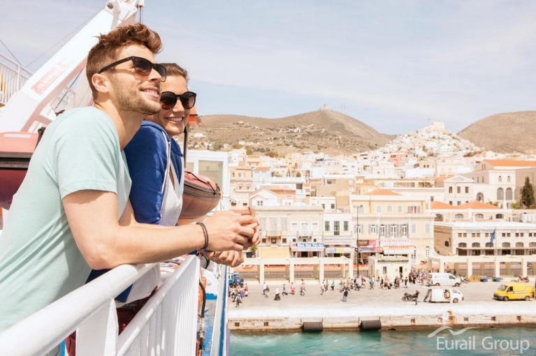 Image of a young couple wearing sunglasses and enjoying the views from aboard a ferry leaving a dusty port city in Greece