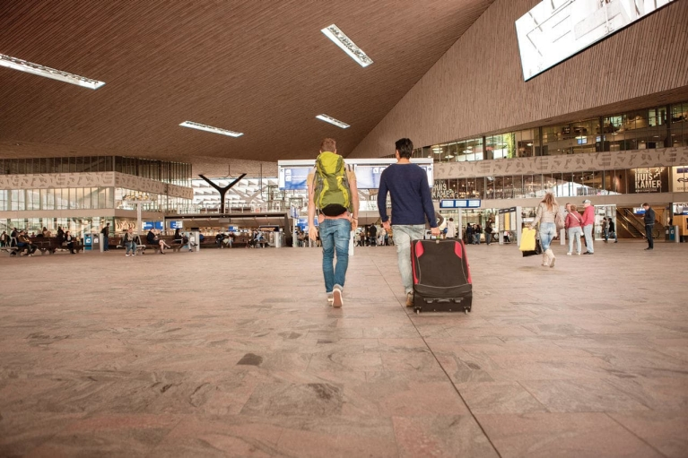 Image of 2 men with a case and backpack walking through a large train station hall