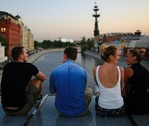 Youth discounts | Group of friends sitting on bridge at sunset